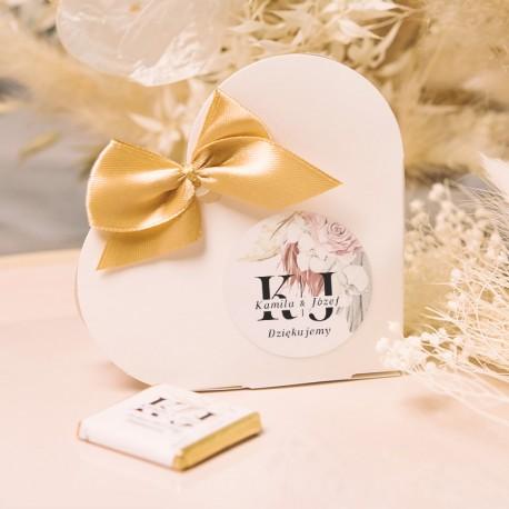 Pudełeczka w kształcie serca ze złotą kokardką oraz etykietą z imionami pary młodej na drobne słodycze dla gości