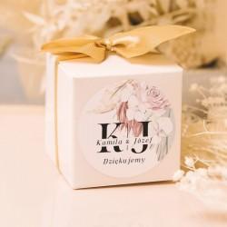 Kwadratowe pudełeczko z kokardką oraz etykietą z imionami pary młodej i datą jako podziękowanie dla gości.