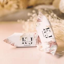 Krówki ślubne w białych papierkach na których widnieją inicjały i imiona młodej pary oraz tekst Dziękujemy