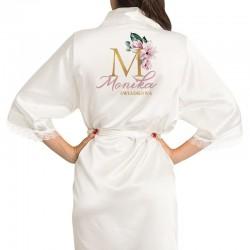 Biały szlafrok z nadrukiem na plecach. Nadruk przedstawia inicjał w kolorze złotym zdobiony kwiatem magnolii. Pod inicjałem umie