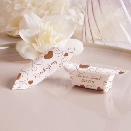 Krówki na beżowym talerzu. Zapakowane w biały papierek w serduszka w kolorze kawowym. Biało-kremowy kwiat w tle.