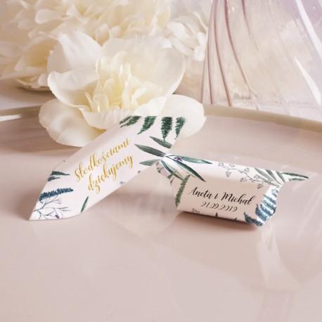 Krówki położone na karmelowym talerzu. Białe papierki dekorowane liśćmi paproci i złotym napisem z podziękowaniem.