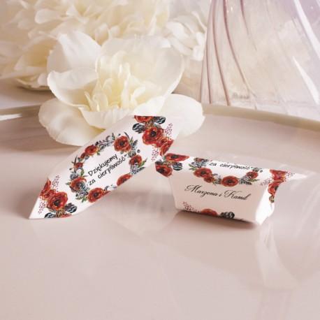 Dwie krówki w białych papierkach zdobionych nadrukiem czerwonych maków. Położone na beżowym talerzu. Z tyłu biało-kremowy kwiat.
