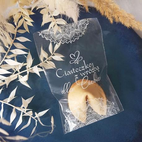 Ciasteczko z wróżbą w przezroczystym opakowaniu z białym napisem Ciasteczko z wróżbą dla Ciebie i zdobieniem w białą koronkę. Ci