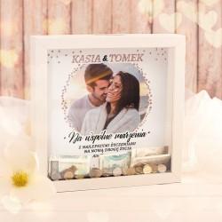 Skarbonka 3d z białą ramą i zdjęciem pary w tle. W środku jest napis na Wspólne marzenia. Prezent na ślub