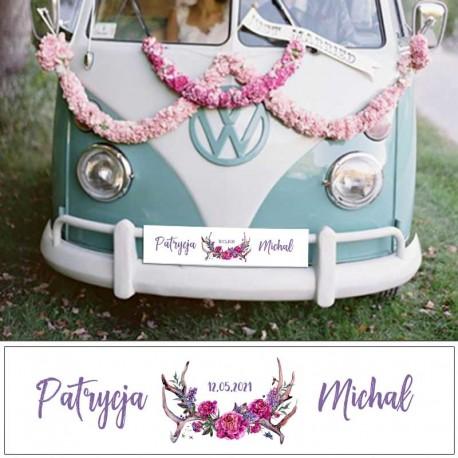 Tablica ślubna na samochód z imionami Pary Młodej. Zdobiona zwierzęcymi rogami dekorowanymi fioletowymi kwiatami w stylu boho.