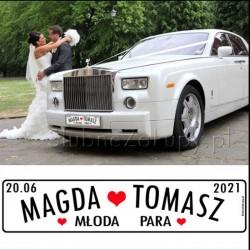 Biała tablica ślubna na samochód. Minimalistyczny design z białym tłem dekorowanym czerwonymi serduszkami.