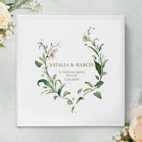 Biały album na ślubne zdjęcia - prezent ślubny dla Młodej Pary. Grafika gałązek z liliami otacza imiona Nowożeńców i datę ślubu.