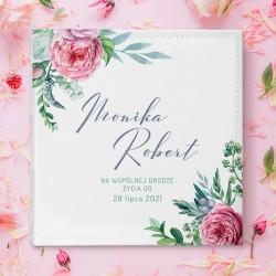 Biały album ślubny na zdjęcia dla Młodej Pary. Okładka zdobiona różowymi kwiatami na białym tle. Imiona Pary Młodej na okładce.