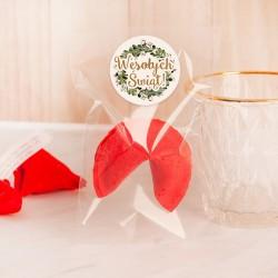 Ciasteczko świąteczne w kolorze malinowym. Przezroczyste opakowanie z etykietą i wiankiem z jemioły.