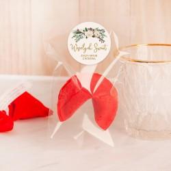 CIASTECZKO w kolorze malinowym. Ciasteczko z wróżbą w celofanowym opakowaniu. Etykieta z życzeniami świątecznymi.