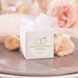 PUDEŁECZKA kwadrat podziękowanie dla gości. Przewiązane białą kokardką. Etykieta z motywem obrączek i imionami Pary Młodej.