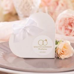 Pudełeczka serca upominek dla gości. Pudełko zamknięte białą kokardką. Etykieta z motywem obrączek i imionami Pary Młodej.