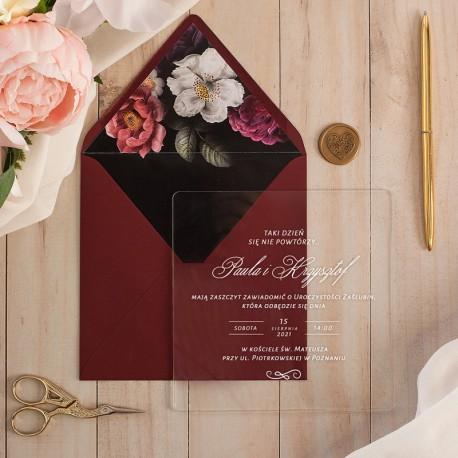 Zaproszenia ślubne na przezroczystej tabliczce ze szkła akrylowego. Biała czcionka tekstu. Bordowa koperta dekorowana kwiatami.