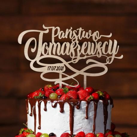 Topper na tort z nazwiskiem Nowożeńców oraz datą przyjęcia. Kolor jasnego drewna. Dekorowany wywijanym ornamentem.