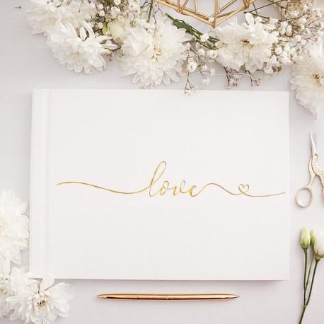 """Księga na wpisy gości weselnych. Biała okładka z dekoracyjnym napisem """"love"""". Metaliczny nadruk z serduszkiem."""