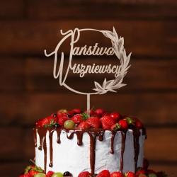 Topper na weselny tort. Wykonany z drewna. Ma kształt okręgu zdobionego z jednej strony listkami. W środku nazwisko nowożeńców.