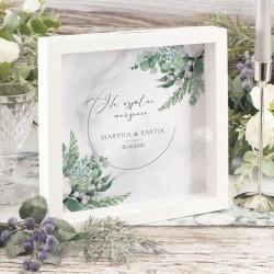 Skarbonka w formie białej ramki 3D z szybką. Tło skarbonki przedstawia zimową grafikę zielonych gałązek i białych kwiatów bawełn