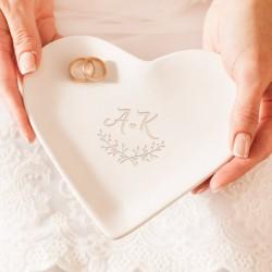 Podstawka ceramiczna w białym kolorze i w kształcie serca. Na powierzchni wzór z inicjałami Pary Młodej oraz dwoma gałązkami.