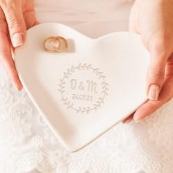 Talerzyk z ceramiki w kolorze białym. Podstawka pod obrączki ma kształt serca i wzór wianka z listkami, który oplata inicjały.