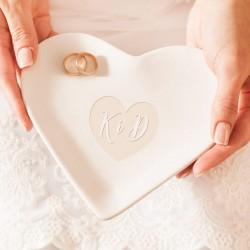 Talerzyk pod obrączki. Ma kształt białego serca i wykonany jest z ceramiki. Wzór wygrawerowanego serca z inicjałami.