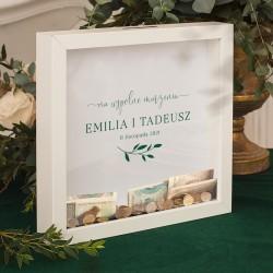 Skarbonka 3D w białej ramie, posiada wewnątrz ozdobną kartę z imionami Pary Młodej i datą uroczystości.