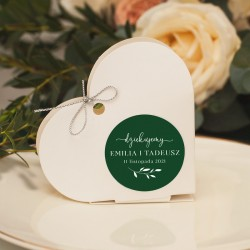 Białe pudełeczka w kształcie serca, wzbogacone są o personalizowane etykiety w kolorze butelkowej zieleni.