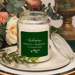 Świeca zapachowa w białym kolorze. Posiada ozdobną etykietę z personalizacją oraz delikatną gałązką w kolorze butelkowej zieleni