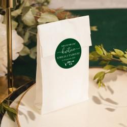 Biała papierowa torebka z ciemnozieloną naklejką. Upominek dla gości weselnych.
