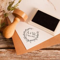 Pieczątka ślubna posiada drewnianą rączkę. Stempel posiada wzór kwiatowego wianka oraz inicjały Pary Młodej.