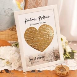 Plakat w białej ramie ze złotym sercem w centralnej części. Nad i pod sercem widnieje dedykacja oraz podpis z imionami pary młod