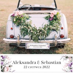 Biała tablica ślubna na auto. Dół dekorowany liliowymi kwiatami, ana środku umieszczone dowolne napisy.
