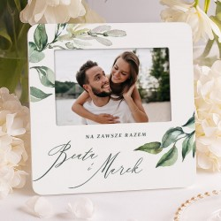 Biała ramka na ślubne zdjęcie. Grafika z gałązkami i zielonymi listkami.