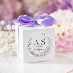 Białe pudełeczka na upominki dla gości. Wzbogacone o personalizowane etykietki z kwiatową grafiką.