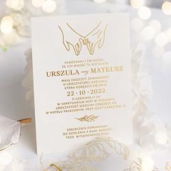 Zaproszenie ślubne ze złoconym nadrukiem w zestawie z ozdobną kopertą przewiązaną złotym sznurkiem.