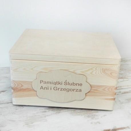 Prezent dla bliskich w postaci kufra na pamiątki ślubne. Skrzynia wykonana jest z jasnego, naturalnego drewna.