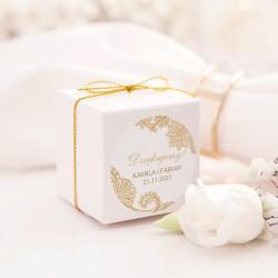 Białe kwadratowe pudełeczka wzbogacone o etykiety. Idealnie sprawdzą się jako uzupełnienie upominku dla gości.